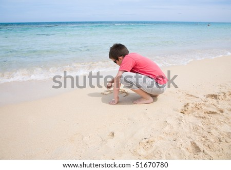 drawing in the sand -- small cute boy in red t-shirt and shorts drawing with his fingers in the smooth wet sand by blue ocean