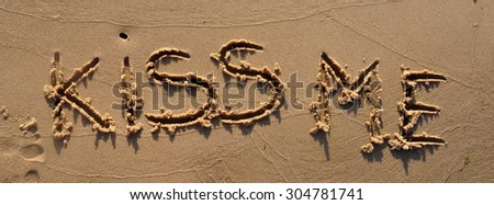 drawing KISS ME on the sand. Beach background. Top view - stock photo