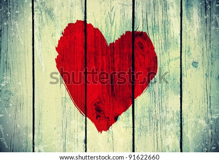drawing love symbol on old wooden wall - stock photo
