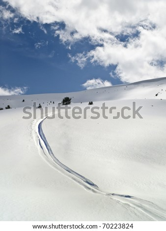 Drawing of a curved line on a slope of virgin snow by a skier - stock photo