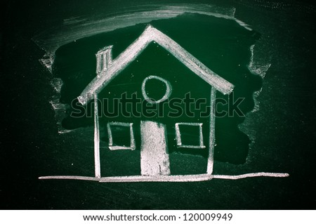 Drawing of a house on a green chalkboard - stock photo