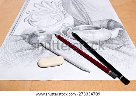 Drawing of still life by graphite pencil with apple, tea infuser and plaster palm leaf. Graphite pencils and eraser on the wooden background. - stock photo