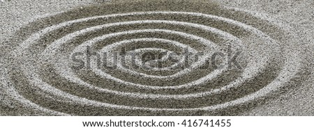 Drawing on the sand in a spiral.