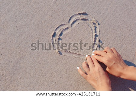 Drawing on white sand beach heart symbol, hands