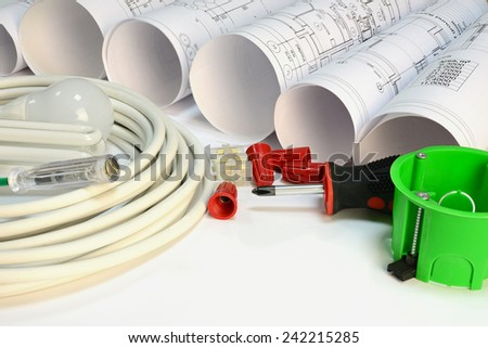 Drawing rolls, socket box, power cable, screwdriver, lamps, test pen, terminal block, wire connectors on white surface - stock photo