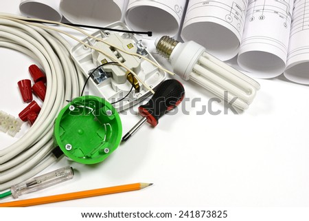 Drawing rolls, wall socket, socket box, power cable, screwdriver, lamp, test pen, pencil, fasteners, wire connectors, terminal block and wires on white surface - stock photo