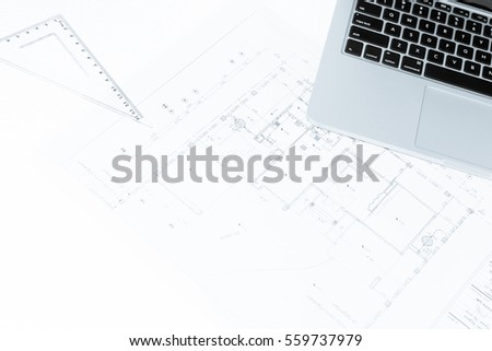 drawing rulers, and notebook over house construction blueprint with blue tone effect, useful for construction, business, architecture, engineering, insurance background concepts