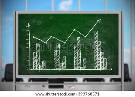 drawing stock chart on green blackboard in office - stock photo
