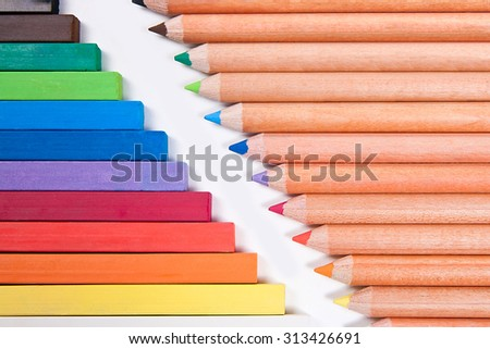 Drawing supplies: assorted color pencils and chalk pastels, isolated on white background. Abstract background from color pencils and chalk pastels. - stock photo