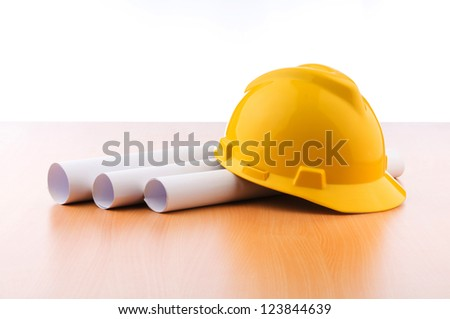 Drawings and hard hat on the desk - stock photo