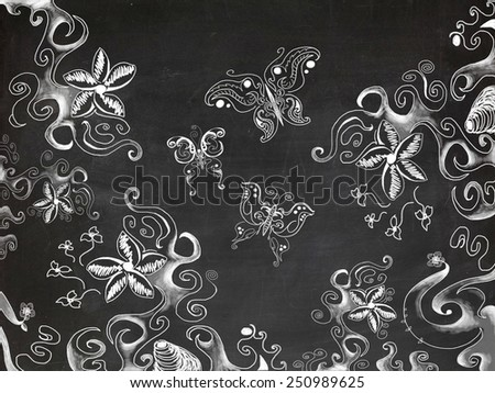 Drawings of various butterflies and floral patterns on chalk board - stock photo