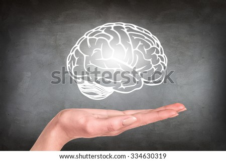 Drawn brain hovered over the human hand on the gray wall background - stock photo