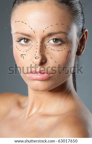 Drawn lines on a  brunette woman's face as marks for facial plastic surgery - stock photo
