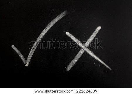 Drawn on the black blackboard white yes tick sign next to a piece of chalk and no - stock photo
