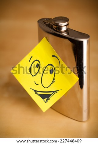 Drawn smiley face on a post-it note sticked on a hip flask - stock photo