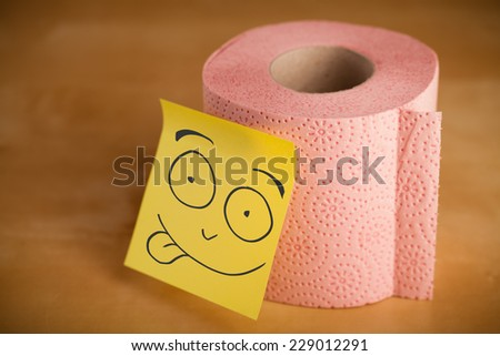 Drawn smiley face on a post-it note sticked on a toilet paper roll - stock photo