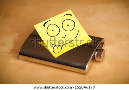 Drawn smilingface on a post-it note sticked on a hip flask - stock photo