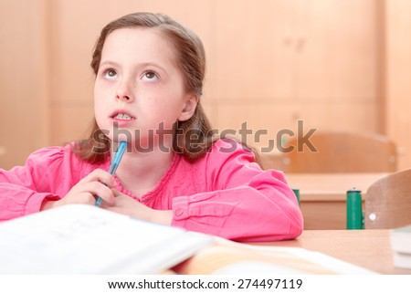 Dream away life. Thoughtful little girl during classes sitting at desk and looking upwards . - stock photo