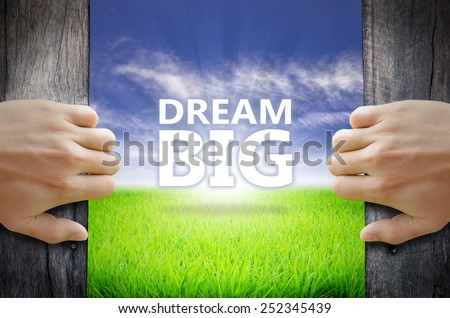 Dream Big motivational quotes. Hand opening an old wooden door and found a texts floating over green field and bright blue Sky Sunrise. - stock photo