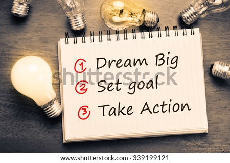 Dream Big - Set Goal - Take Action, handwriting on notebook with light bulbs - stock photo