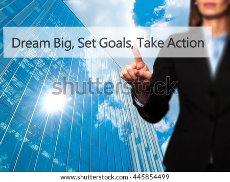 Dream Big Set Goals Take Action - Businesswoman hand pressing button on touch screen interface. Business, technology, internet concept. Stock Photo