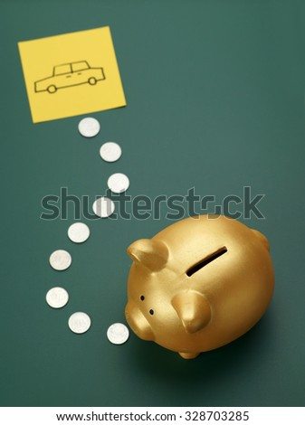 Dream car savings - golden piggy bank, coins and car sketch on blackboard - stock photo