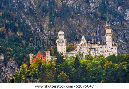 Dream castle Neuschwanstein of bavarian king in Germany, hanging on a cliff with a mountain in background, in autumnal light - stock photo