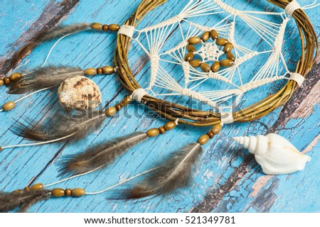 Dream catcher with feathers on blue shabby wooden background. Nautical decor with shells