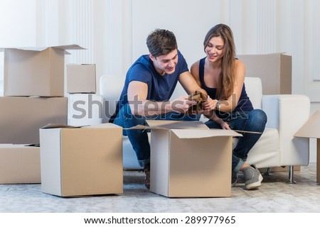 Dream come true, moving. Loving couple enjoys a new apartment and keep the box in his hands while young and beautiful couple in love sitting on the couch in an empty apartment among boxes - stock photo