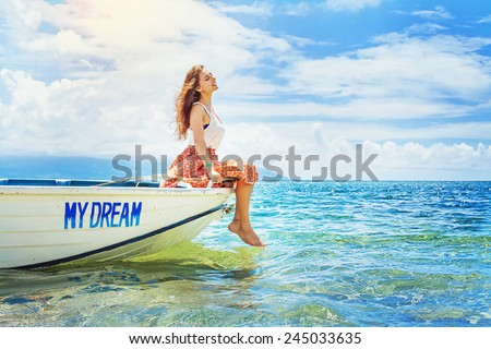dream concept: woman sitting in a beautiful boat - stock photo