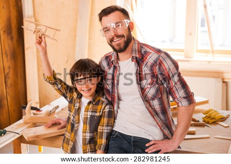Dream creators. Cheerful little boy holding wooden plane while standing with his father in workshop - stock photo