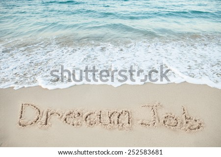 Dream Job written on sand by sea at beach - stock photo