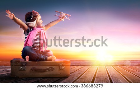 Dream journey - Little Girl On Suitcase At Sunset   - stock photo