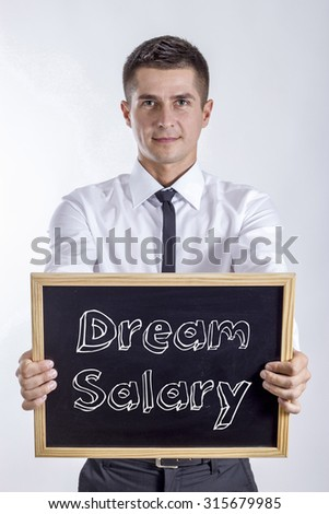 Dream Salary - Young businessman holding chalkboard with text - stock photo