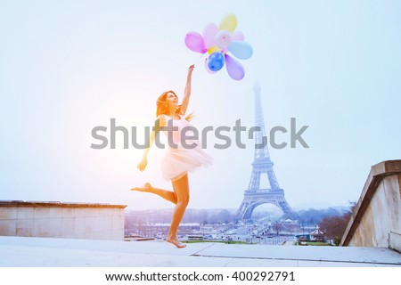 dream travel, girl with balloons jumping near Eiffel Tower in Paris - stock photo