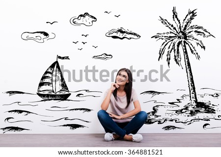 Dreaming about vacation. Cheerful young woman smiling while sitting on the floor with illustration in the background - stock photo