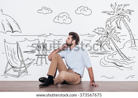 Dreaming about vacation. Young handsome man keeping hand on chin and looking away while sitting on the floor with illustration of resort in the background - stock photo