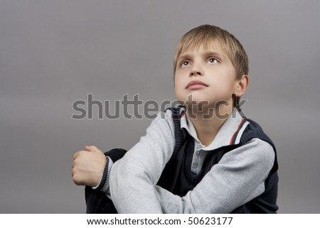 dreaming and relaxing blond caucasian boy with eyes lifted and hands crossed in front isolated over gray background