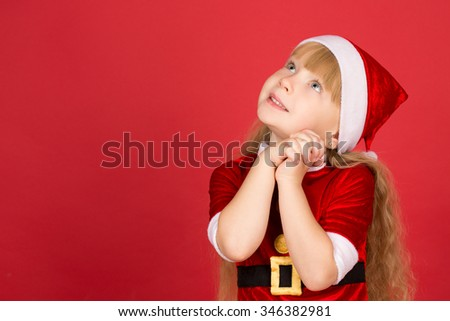 Dreaming big. Cheerful little girl wearing Santa Claus outfit looking up dreamily and smiling copyspace on the side - stock photo