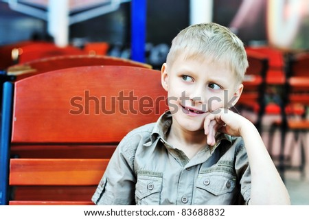 dreaming boy sitting on the wooden chair
