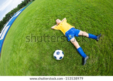Dreaming boy soccer player lying on natural grass. Fish-eye lens. - stock photo