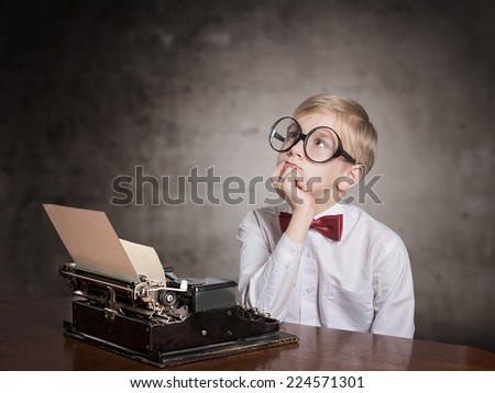 Dreaming boy with the typewriter. Retro style portrait - stock photo