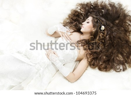 Dreaming bride with long curly hair lying down over white. Sleeping beauty. High angle view. - stock photo