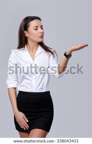 Dreaming business woman blowing on palm, looking at copy space on her palm, over grey background - stock photo