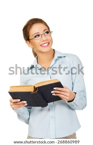 Dreaming business woman holding a book. - stock photo