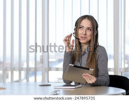 Dreaming female customer support officer. Portrait of smiling cheerful customer support phone operator in headset talking to customer. - stock photo