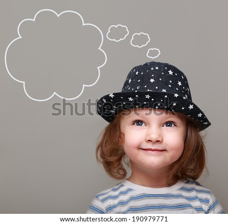 Dreaming kid girl in hat looking up on empty bubble above on grey background - stock photo