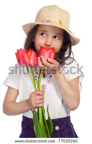 Dreaming little girl in straw holding red tulips