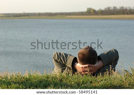 Dreaming man on the river bank - stock photo