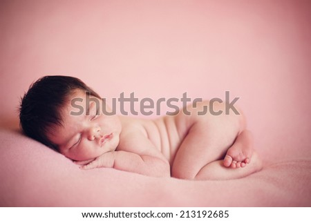Dreaming Naked Newborn Baby Sleeping on soft Pink Blanket